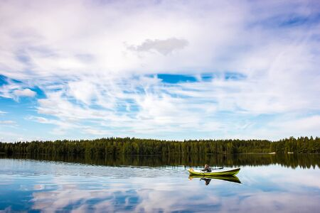 Fisherman sails on a green boat on the lake Stock Photo - 15609213