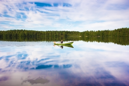 green boat: Fisherman sails on a green boat on the lake Stock Photo