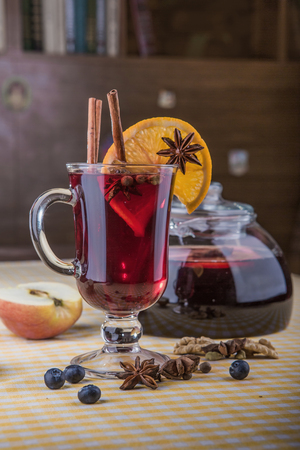 a glass of mulled wine decorated with cinnamon sticks and a slice of orange, in the foreground and in the background - a pitcher of mulled wine.