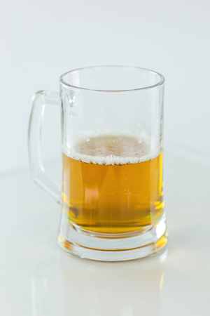 Beer glass half full on white background
