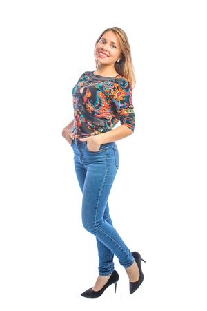 Attractive girl in bright blouse and shoes and jeans posing smiling