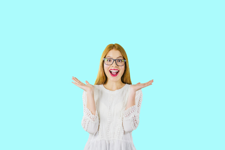 Attractive girl in a dress with red hair and bright makeup in surprise raises her hands on an isolated background 写真素材
