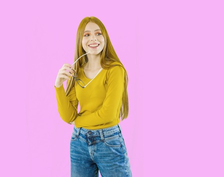Cheerful girl with long red hair with glasses in her hands with smile looks away on an isolated background 版權商用圖片