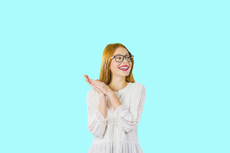 Young beautiful girl with long red hair in glasses with folded palms together smiling pretty looking to the side, photo on an isolated background Stock Photo