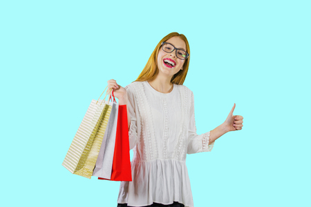 Portrait of a young beautiful red-haired girl in glasses and with packages of new purchases or gifts, which shows the emotions of joy looking into the camera and shows the class, photo on an isolated background Banco de Imagens