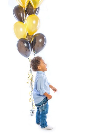 A little dark-skinned boy with curly hair stands in profile next to the balloons and looks away shouting out, isolated background