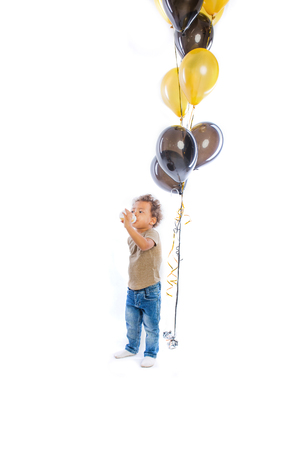 A little dark-skinned baby with curly hair stands out from a bottle and looks to the side, in the background there are balloons, an isolated background 版權商用圖片