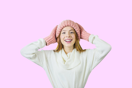 Young cute red-haired teen girl in a knitted pink hat and mittens is holding her head with her hands and smiling peacefully on an isolated pink background, the girls emotions, winter holidays and holidays