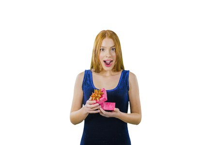 A cute young red-haired girl in a blue velvet evening dress with a box in her hands joyfully smiles and looks into the camera on an isolated background, a marriage proposal, a surprise effect