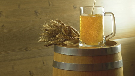Beer barrel and beer glasses with wheat on wooden table.