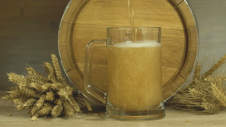 Oktoberfest.Beer is poured into a glass and the foam is drained Stock Photo
