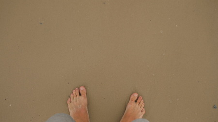 Close-up as the legs of a man go leisurely barefoot on a golden sandy beach.