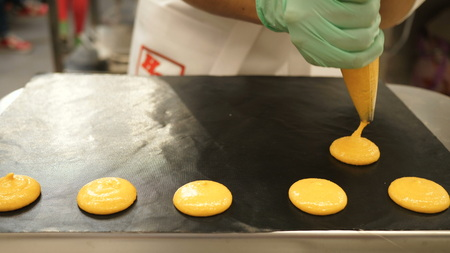 Process of making macaron macaroon, french dessert, squeezing the dough form cooking bag. Food industry, mass or volume production
