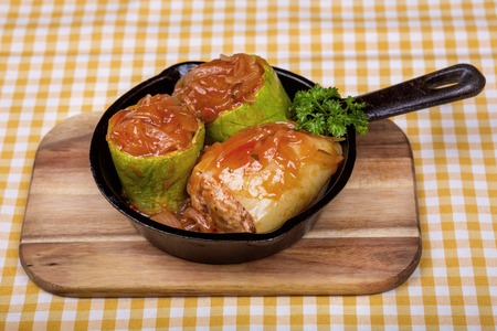Zucchini stuffed with rice and meat, served in a mini frying pan on a wooden board. Side view