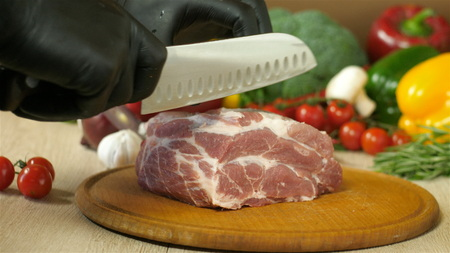 Chef with black gloves takes a knife and regulates a piece of raw juicy meat lying on a round wooden board, next there is another round wooden board to a piece of meat, in the background vegetables greens, broccoli, red pepper, red onion, garlic, cherry tomatoes, branches of rosemary and thyme, the background is blurred, the side view