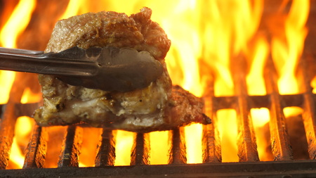 The chef turns over the grilled steak several times with tongs and looks at how much he was fried.