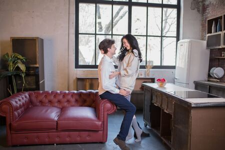 Beautiful Smiling Teenager Girl Hugs a Guy near the sofa couch in the kitchen