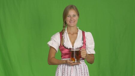 Oktoberfest. Smiling girl with beer on green