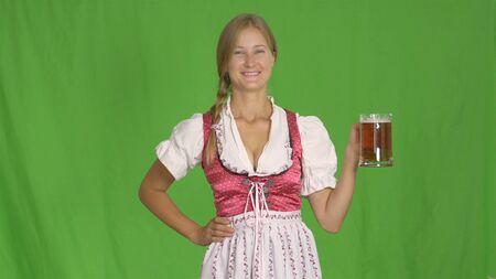 Oktoberfest. Girl wiht mug of beer on green
