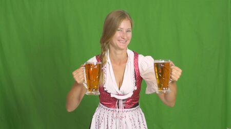 Oktoberfest. Girl puts two mugs of beer on green background 版權商用圖片