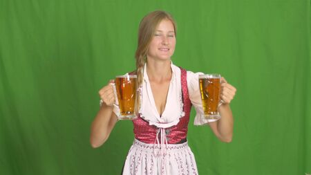 Oktoberfest. Girl puts two glasses of beer on green