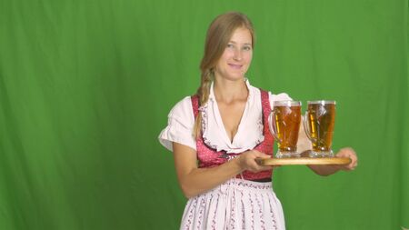 Oktoberfest girl puts two glasses of beer on a wooden table on green background 4k.