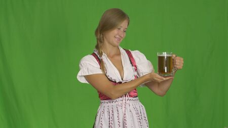 Oktoberfest. A girl in a national costume of Bavaria holds a glass of beer and smiles demonstrating it, a green screen