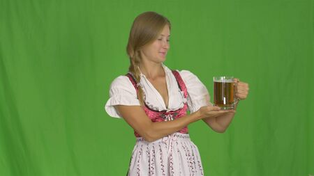 Oktoberfest. Girl with beer on green