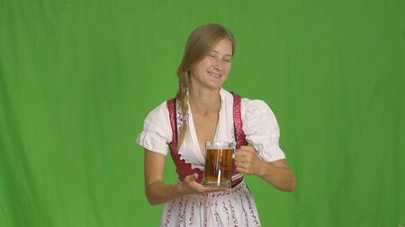 Oktoberfest Girl puts two glasses of beer on wooden table.