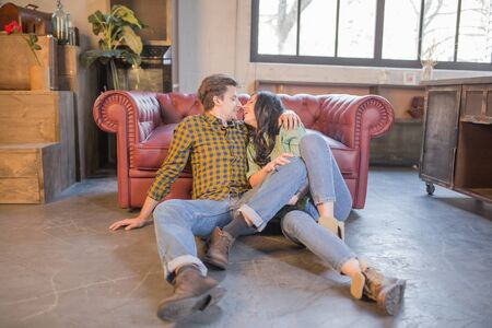 Beautiful Loving Guy and Girl Kiss near the sofa