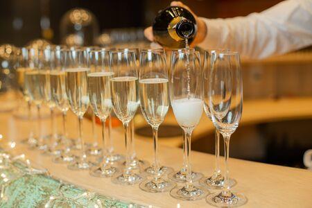 Clous up sparkling champagne bottle filling goblets with wine. 版權商用圖片
