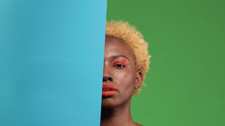 African American with bright makeup half face covered with blue paper