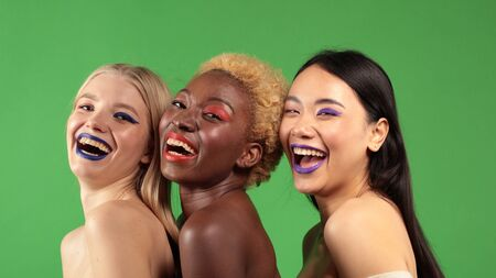 International women smiling at half-turn makeup with European, Asian and African American women with multi-colored makeup