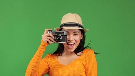 Close up image of traveler making photo of something on green background