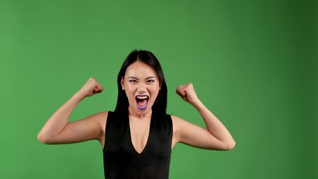 Actively aggressive young woman raising her arms up showing her biceps