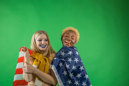Beautiful patriotic vivacious young women wrapped in American flag on an isolated background. United States Independence Day concept. 版權商用圖片