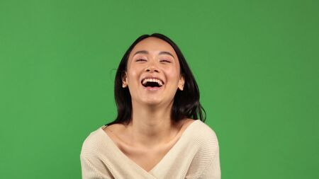 Beautiful young cheerful funny Asian girl happily smiles into the camera portrait with a natural skin tone with minimal amount of makeup on her face. A concept of a positive mood, a mood for joy, fun and thinking about the party. 版權商用圖片