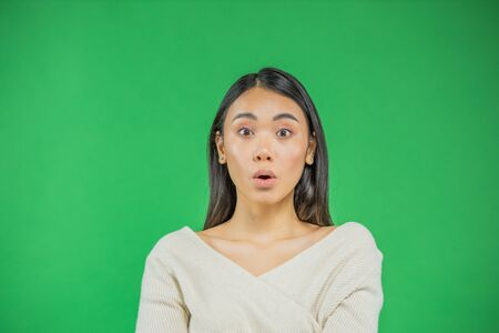 Surprise asian young woman pointing up isolated on green.