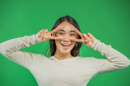 Portrait of an attractive young asian woman holds hands near his eyes green background