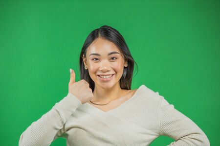 Anattractive young asian woman showing thumbs up over green background