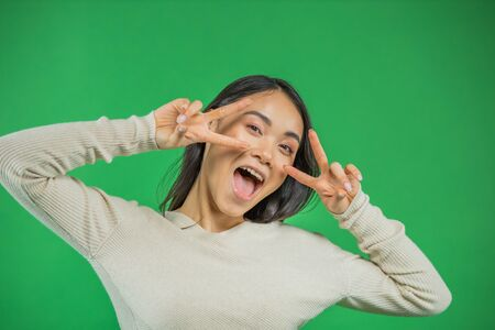 Attractive young Asian woman showing two fingers on both hands holding them near her face