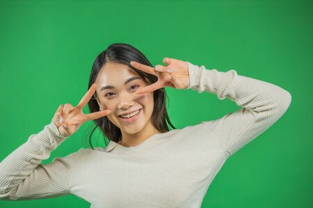 Elegant graceful glamor, attractive pretty calm Asian lady, isolated on a background of green glitter holding her v sign on two hands near her eyes, makes a lovely radiant smile 版權商用圖片