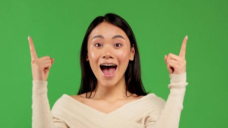 Beautiful Asian woman wearing white blouse over isolated background sign of success making positive hand gesture, pointing fingers smile and happy. Looking at the camera with a cheerful expression, the winner 版權商用圖片