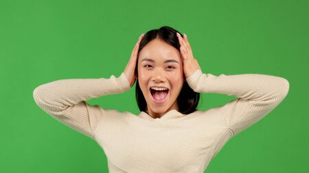 Happy attractive young asian girl holding her head in her arms and having fun shouting, positive emotions of women, victory