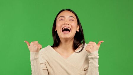 Beautiful woman portrait showing thumbs up, isolated over green background, asian positive young woman 版權商用圖片