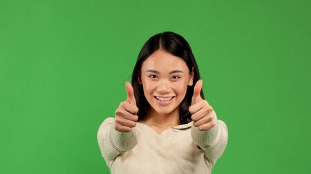 Beautiful woman portrait showing thumbs up isolated over green background, victory, victory concept