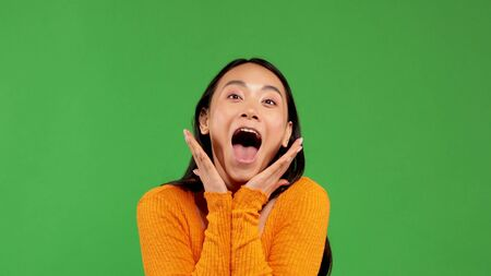 Cheerful cry of young asian woman in bright blouse holds her hands near face without touching face