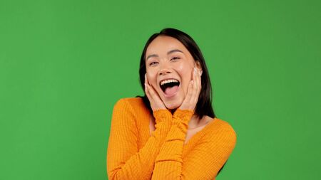 Happy asian woman holding her face with her mouth open