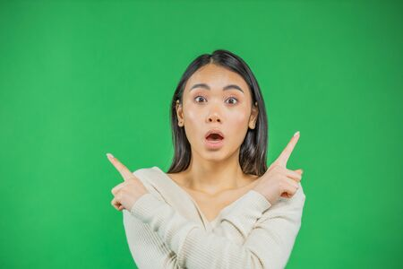 Smiling young asian woman in knitted shirt pointing over head and looking standing with thoughts before choosing. Waist up studio shot on green background