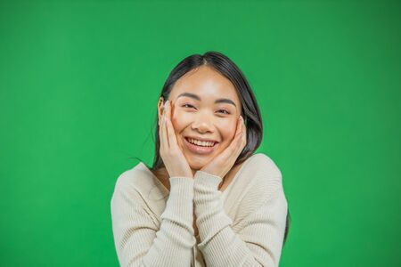Surprised, excited smiling woman on green background. A cheerful multi-faceted Asian , Chinese female model is joyful